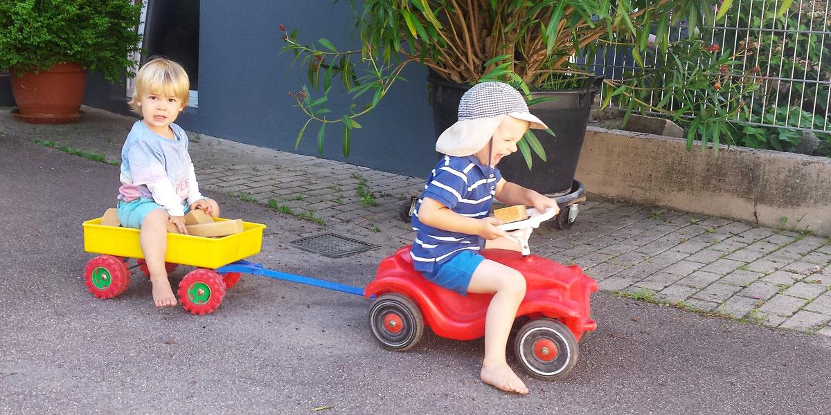 Kinder spielen mit Bobbycar