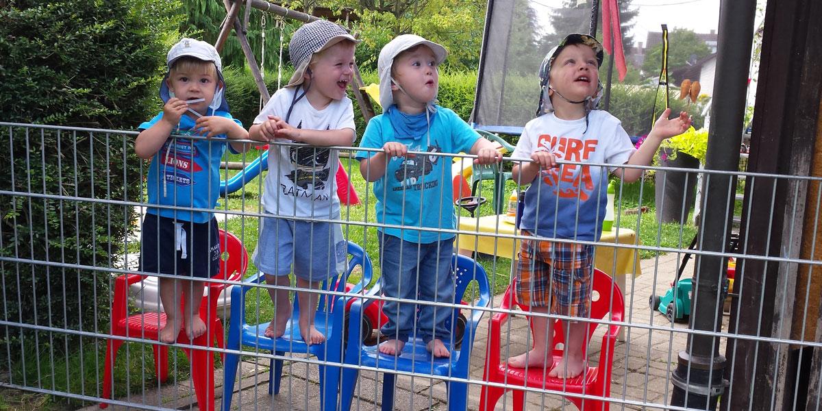 Kinder haben Spaß im Garten auf Stühlen